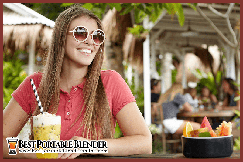 girl-enjoying-tropical-smoothie-in-a-restaurant-best-portable-blender-online